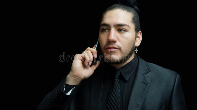 Young latino man in black suit, black shirt, black tie stock photo