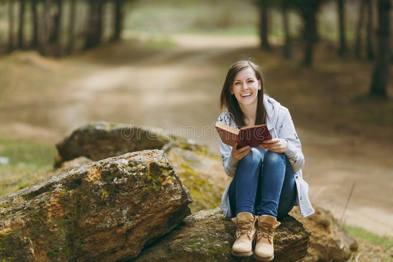 Young laughing beautiful woman in casual clothes sitting on stone studying reading book in city park or forest on green royalty free stock image