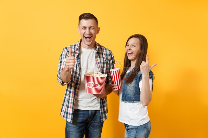 Young laughing couple woman man watching movie film on date hold bucket of popcorn plastic cup of soda cola showing royalty free stock photography