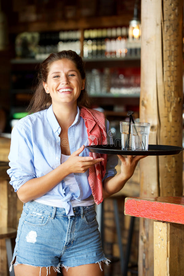Young laughing female server with tray of drinks stock image