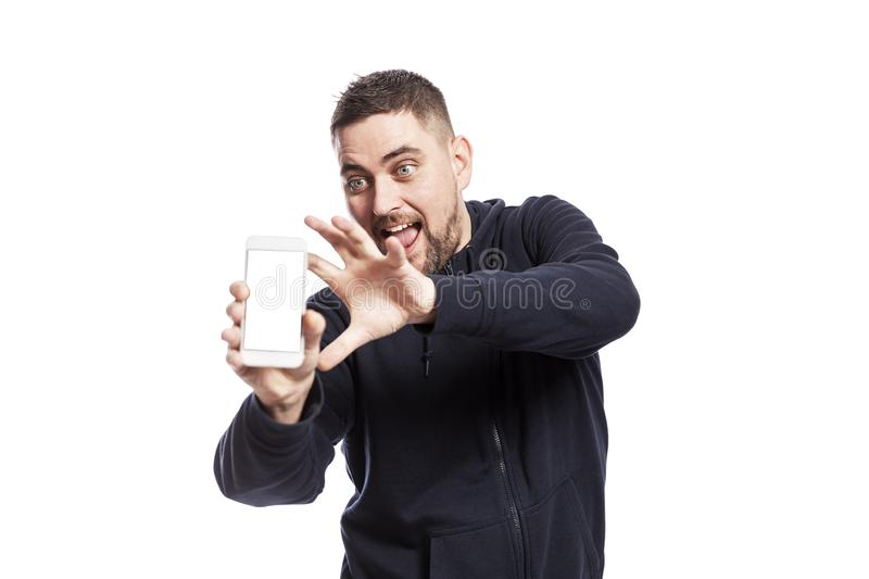 Young laughing handsome man shows on the phone screen. Space for text. Isolated over white background royalty free stock image