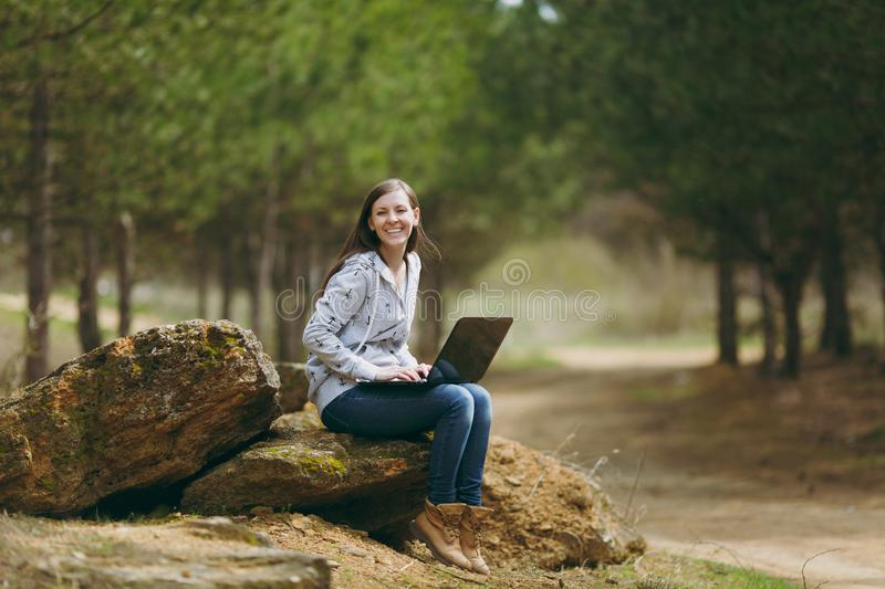 Young laughing successful smart business woman or student in casual clothes sitting on stone using laptop in city park stock photo