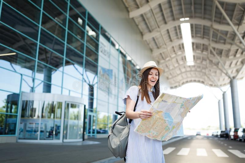 Young laughing traveler tourist woman with backpack holding paper map at international airport. Female passenger. Traveling abroad to travel on weekends getaway royalty free stock photography