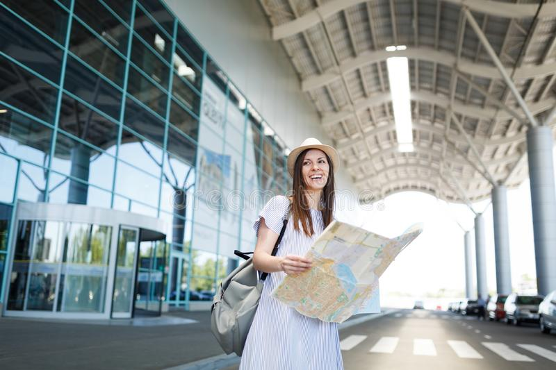 Young laughing traveler tourist woman in light clothes holding paper map at international airport. Female passenger. Traveling abroad to travel on weekends stock photography
