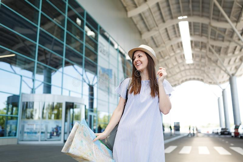 Young laughing traveler tourist woman in light clothes holding paper map at international airport. Female passenger. Traveling abroad to travel on weekends royalty free stock photo