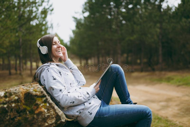 Young laughing woman in casual clothes sitting on stone listening music with headphones and tablet pc computer in city. Park or forest on green blurred stock images