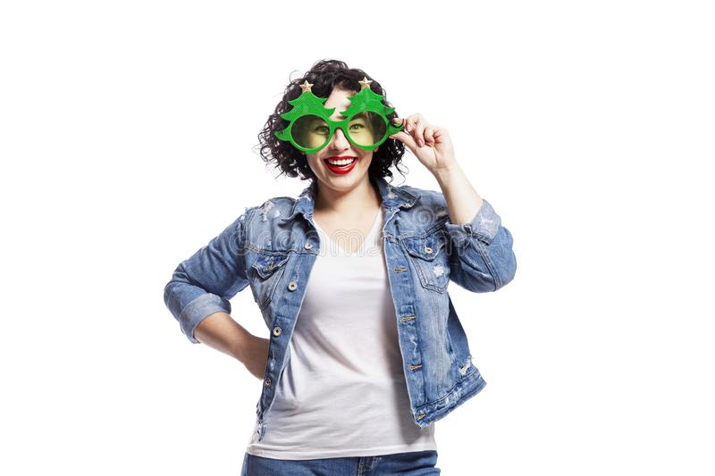 Young laughing woman in funny new year glasses. Bright brunette plus size with curly hair and red lips in jeans. Isolated over stock photos