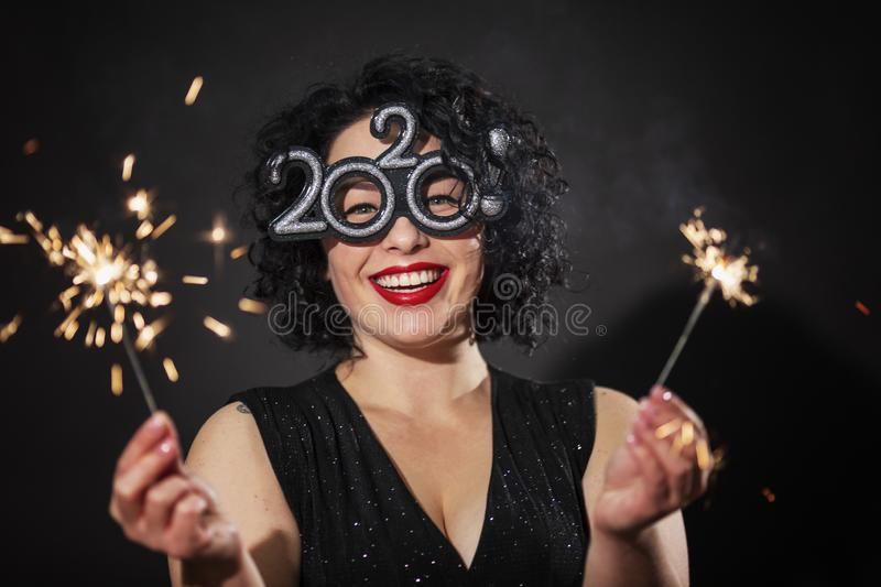 Young laughing woman with sparklers. Brunette with curly hair. New Year celebration. Black background. Close-up royalty free stock images