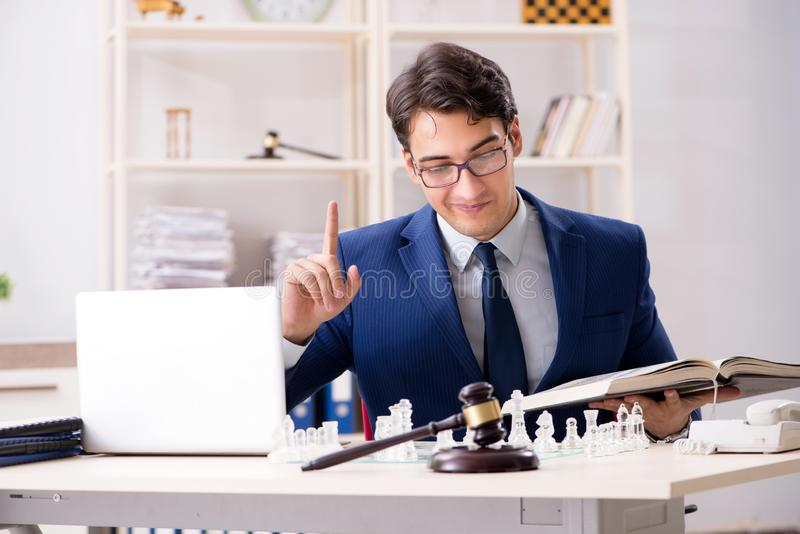 Young lawyer playing chess to train his court strategy and tacti. Cs stock photo