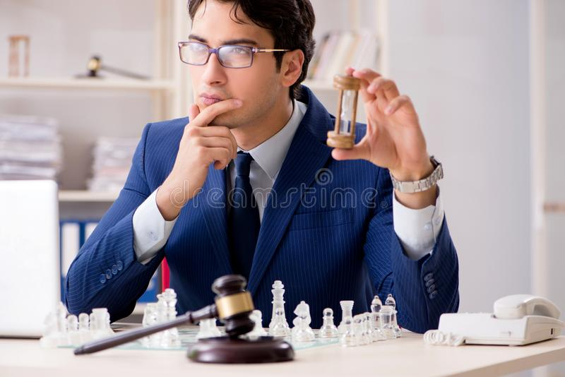 Young lawyer playing chess to train his court strategy and tacti. Cs stock photography