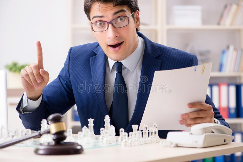 Young lawyer playing chess to train his court strategy and tacti. Cs stock photos