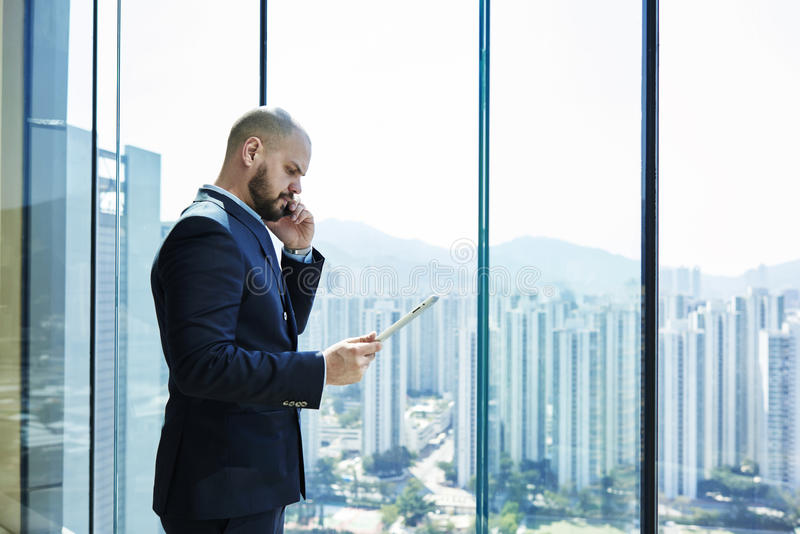 Young lawyer with serious face and digital tablet in hand is talking on mobile phone with client. Businessman is standing in office interior near window with stock photos