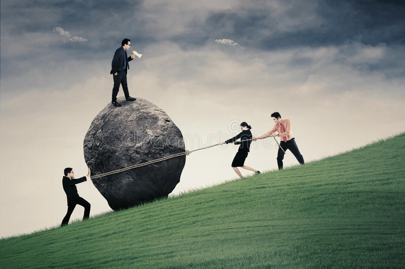 Young leader and his team on the hill. Image of male business leader with megaphone commanding his team for pulling big stone with rope on the hill stock photos