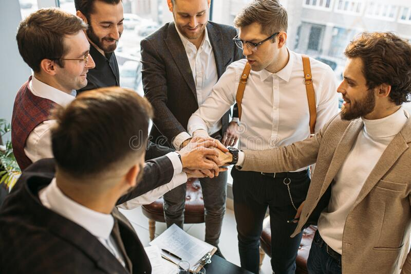 Young leaders joined hands in office stock image