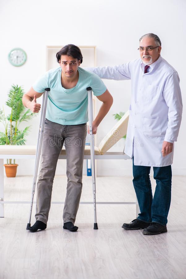 Young leg injured male patient visiting old doctor stock photo