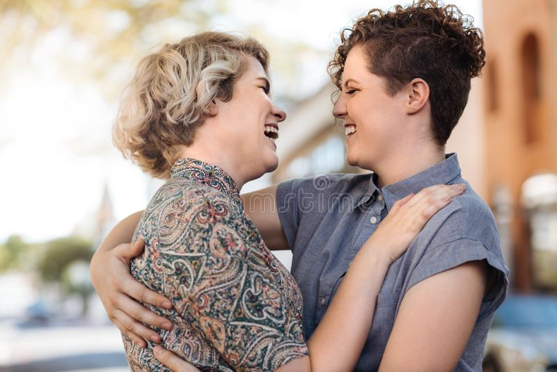 Young lesbian couple laughing while listening to music outside stock photography