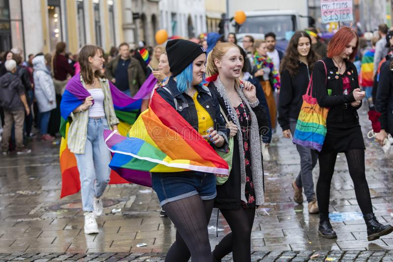 Young lesbian couple with a rainbow flag attending the Gay Pride parade also known as Christopher Street Day CSD in Munich. 2019: Young lesbian couple with a royalty free stock photography