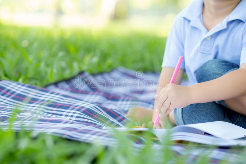 Young little asian boy reading and writing book in the park, asia kid homework and study in the summer. Child relax with drawing on notebook in vacation royalty free stock photo