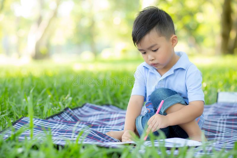 Young little asian boy reading and writing book in the park, asia kid homework and study in the summer, child relax with drawing stock images
