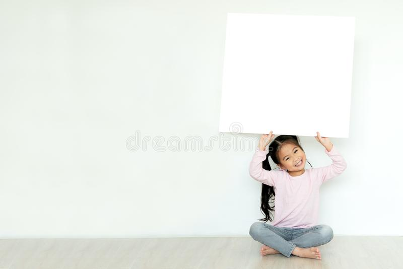 Young little asian girl or kid enjoy holding empty white placard board for media banner, business content presentation, mock up royalty free stock images