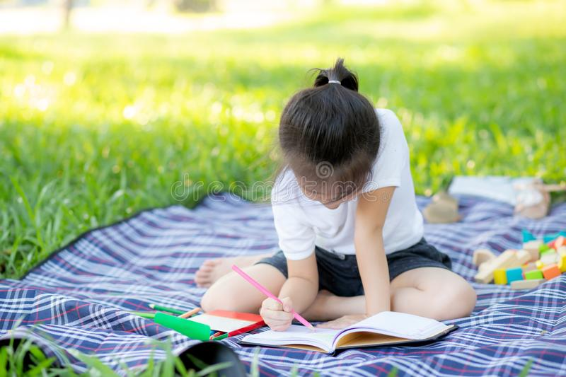 Young little asian girl reading and writing book in the park, asia kid homework and study in the summer stock photography