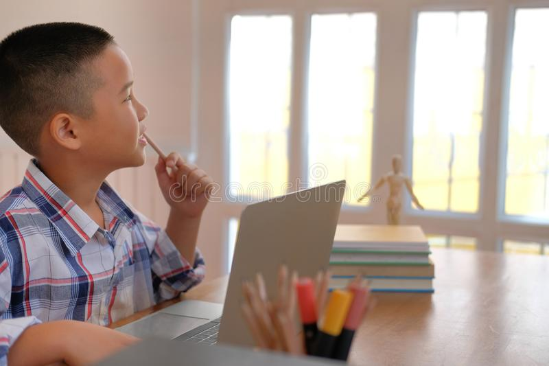 young little asian kid boy child children schoolboy thinking stock image