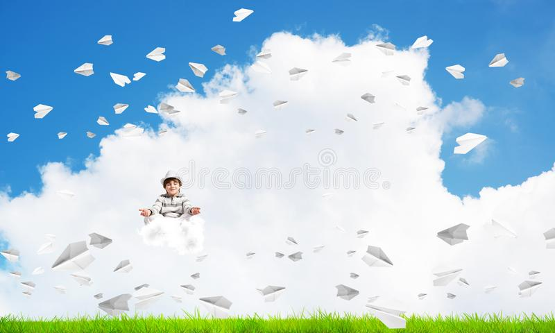 Young boy keeping mind conscious. Young little boy keeping eyes closed and looking concentrated while meditating on cloud among flying paper planes with bright royalty free illustration