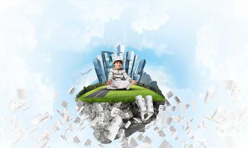 Little boy keeping mind conscious. Young little boy keeping eyes closed and looking concentrated while meditating on flying island among flying papers with royalty free illustration