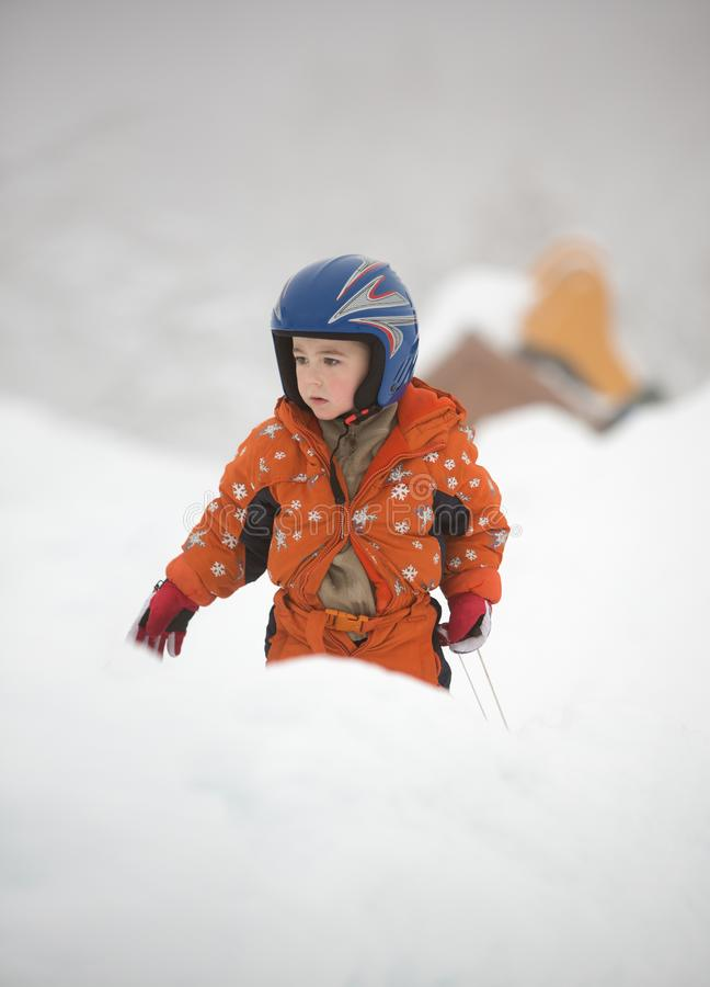 Young little boy in orange overall and blue helmet plays outdoor at winter time. stock image