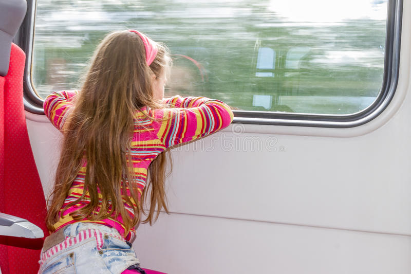 Young little caucasian girl traveling by train royalty free stock photo