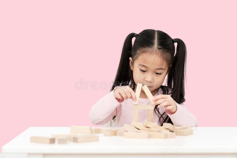 Young little cute asian girl build a house from wooden block construction, wood toy, jenga house on desk in isolated pink royalty free stock photos