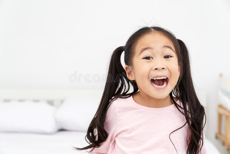 Young little cute asian girl smiling and laughing fun feeling excited, lucky and enjoy weeken in white room background with close stock photo