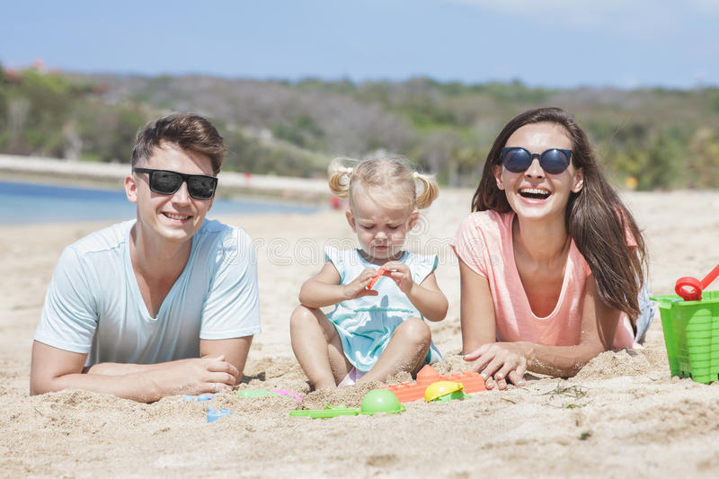 Young little family having fun together on the beach royalty free stock photography