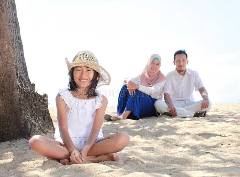 Young little girl in the beach smiling with her parent as background royalty free stock photography