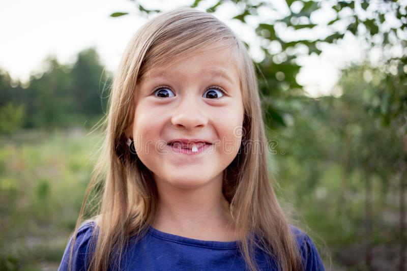 Young little girl without a front tooth. In the countryside stock photo