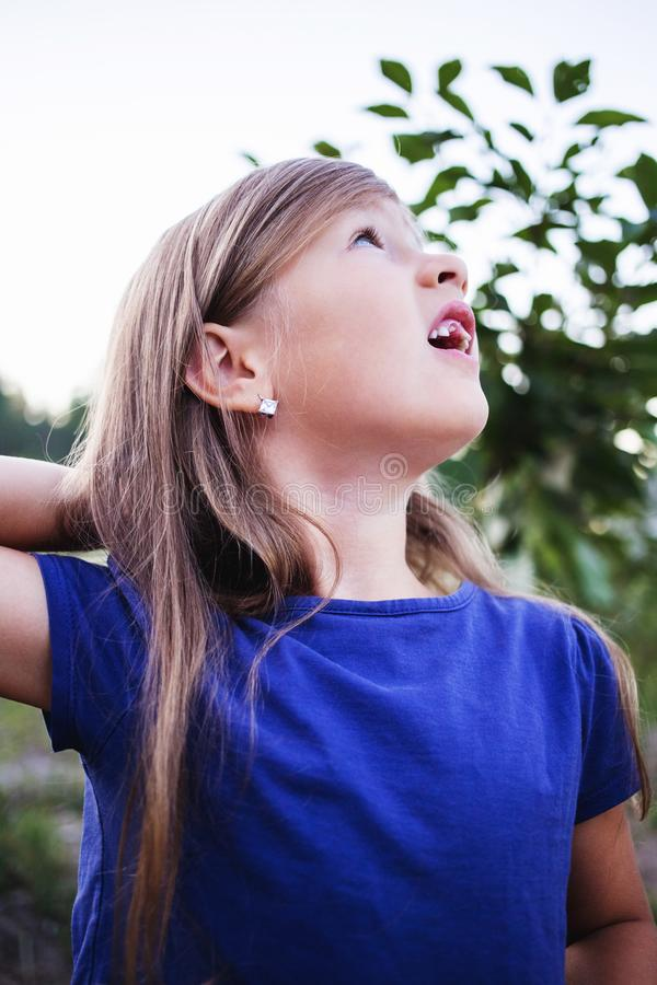 Young little girl without a front tooth. In the countryside royalty free stock photography