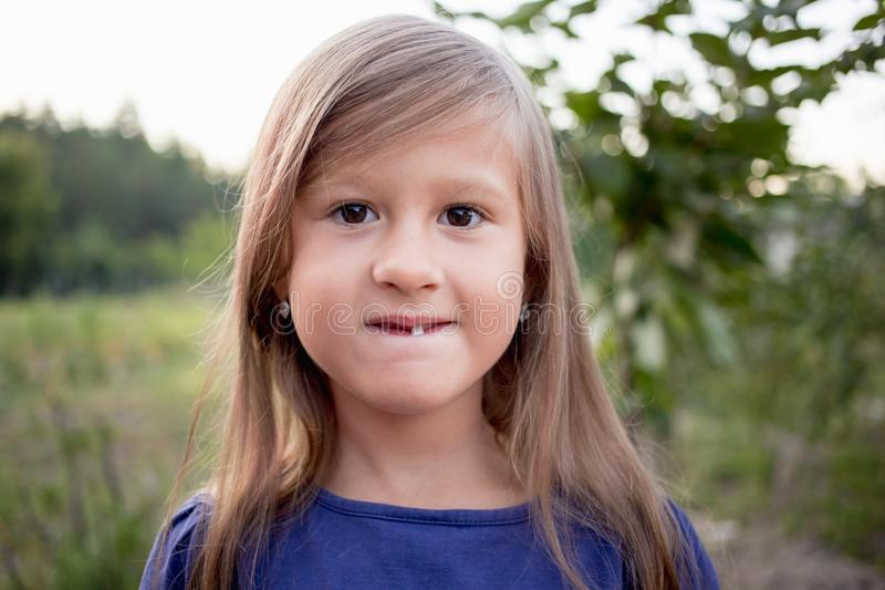 Young little girl without a front tooth. In the countryside royalty free stock photos