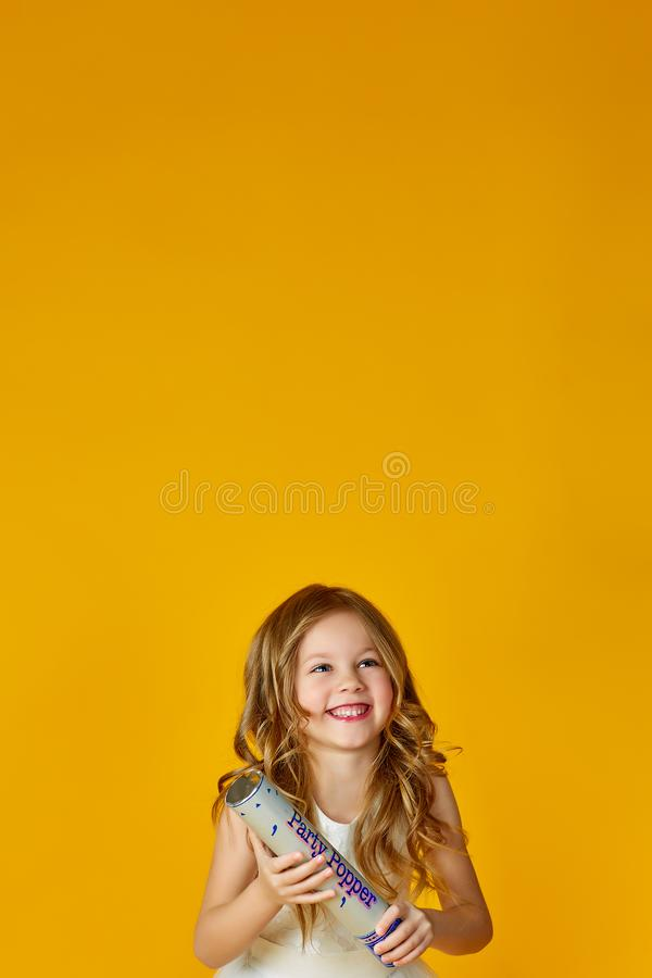 Young little girl having fun with confetti over yellow background. Fun and lifestyle concept royalty free stock images