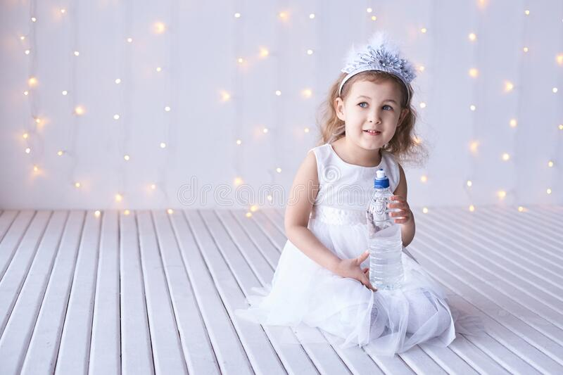 Young little girl hold water bottle. Kid drink cold fresh. Thirsty female person.  stock images