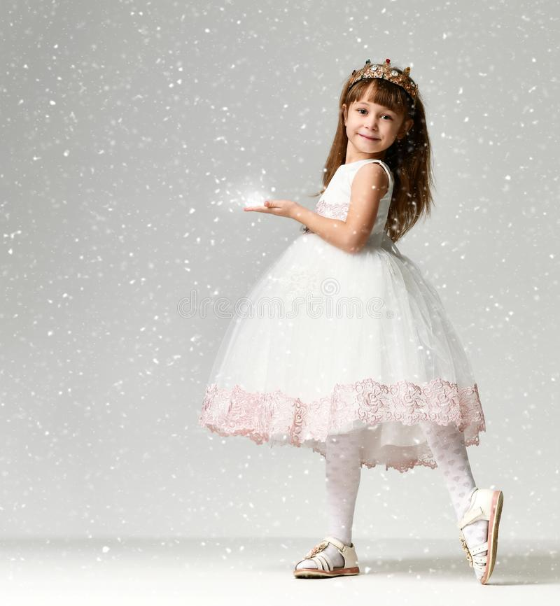 Young little girl model in the white communion winter dress stands in gold crown with expensive gems. Under heavy snow in studio on grey background royalty free stock images