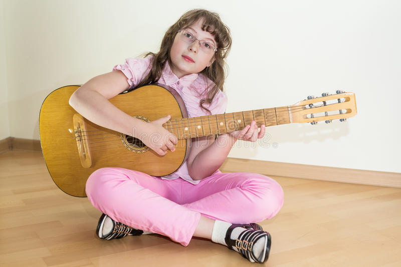 Young little girl playing acoustic guitar royalty free stock image
