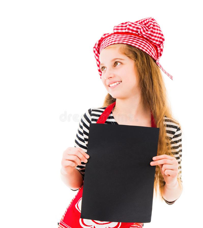 Little girl holds blank sheet of paper. Young little girl in red chef uniform holds vertical blank black sheet of paper and smiles isolated on white background royalty free stock photos