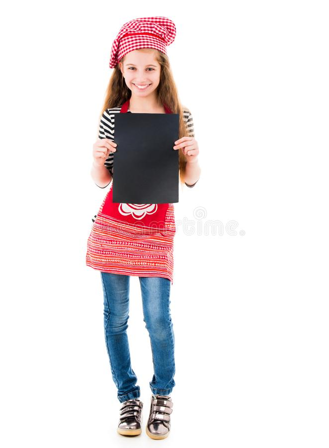 Little girl holds blank sheet of paper. Young little girl in red chef uniform holds vertical blank black sheet of paper and smiles isolated on white background royalty free stock image