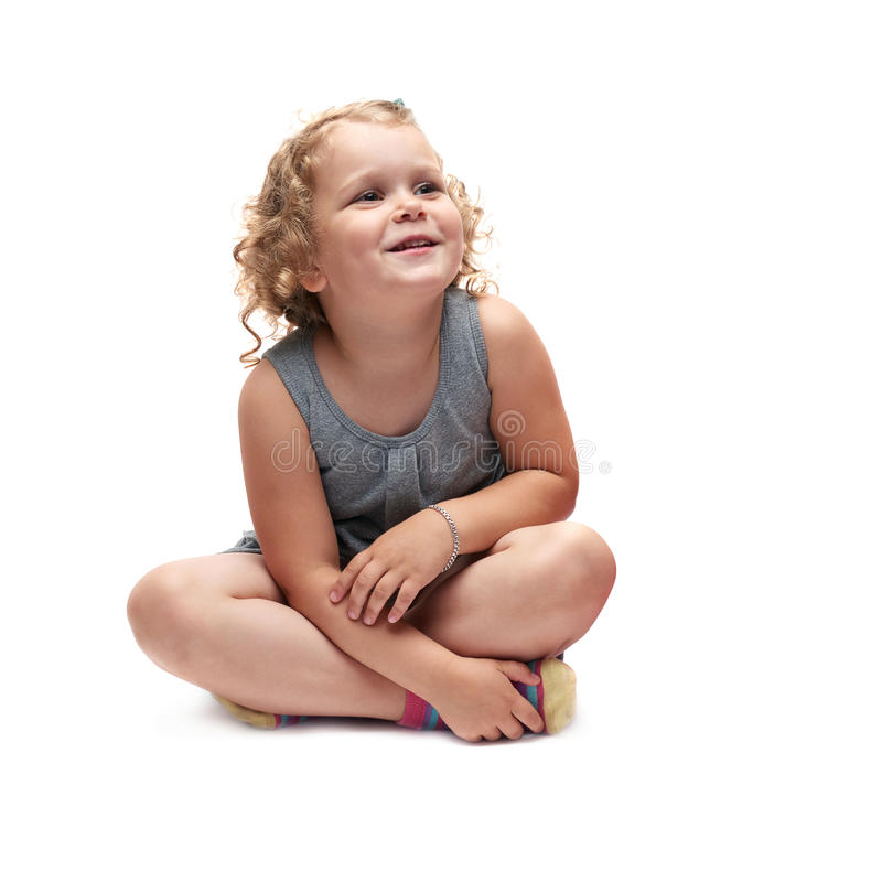 Young little girl sitting over isolated white background stock image