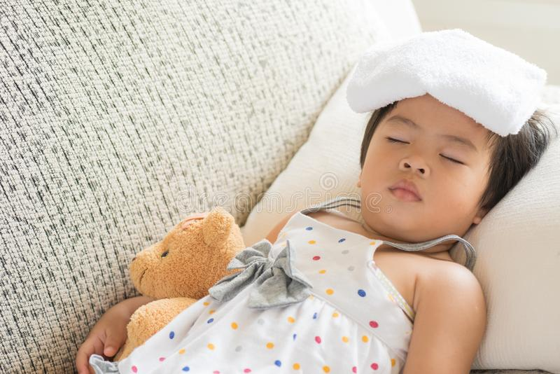 Young little girl sleeping and sick on the sofa with cooler gel. On her head and measuring temperature by thermometer. and take care by her mom royalty free stock photography