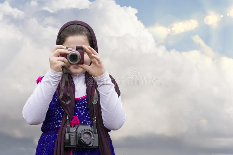 Young Little Girl Is Taking Photograph by Point and Shoot Digital Camera. In front of Blue Sky with Clouds. An old Analogue Camera Strapped on Her Neck stock photography