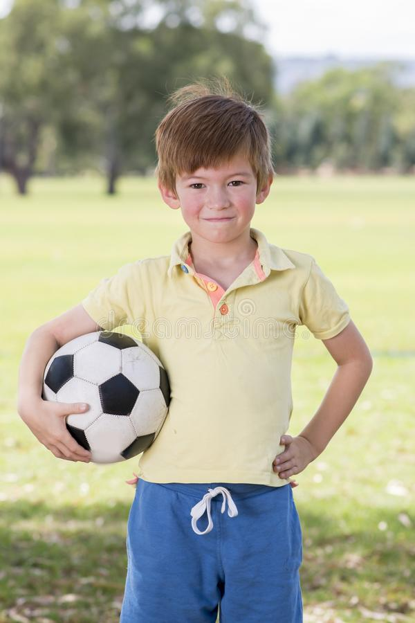 Young little kid 7 or 8 years old enjoying happy playing football soccer at grass city park field posing smiling proud standing ho. Lding the ball in childhood stock image