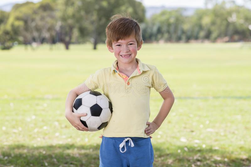 Young little kid 7 or 8 years old enjoying happy playing football soccer at grass city park field posing smiling proud standing ho. Lding the ball in childhood stock photography