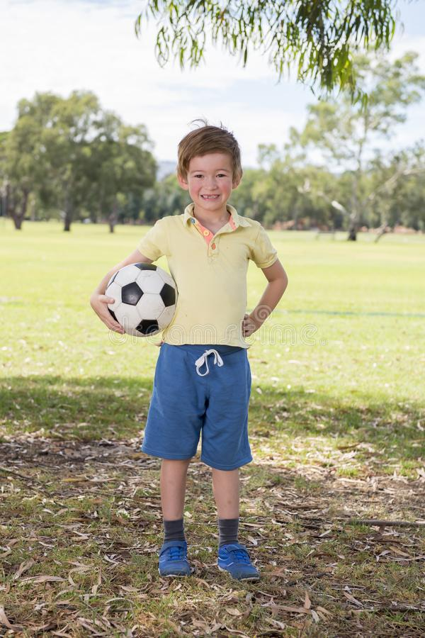 Young little kid 7 or 8 years old enjoying happy playing football soccer at grass city park field posing smiling proud standing ho royalty free stock photography