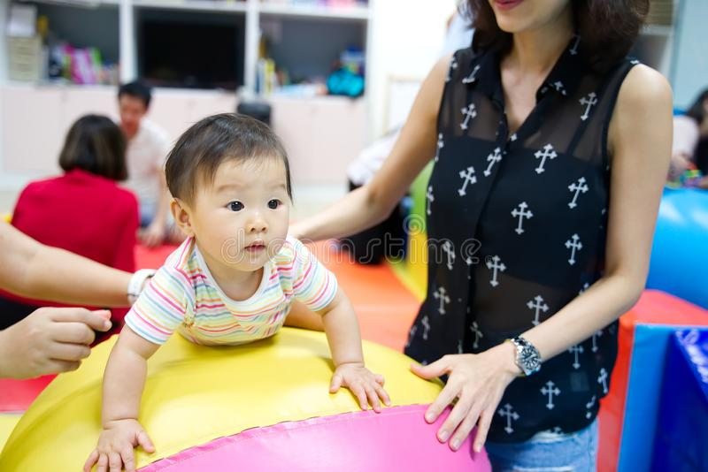 Young little Asian baby enjoy playing on colorful ball in kid playground. royalty free stock image